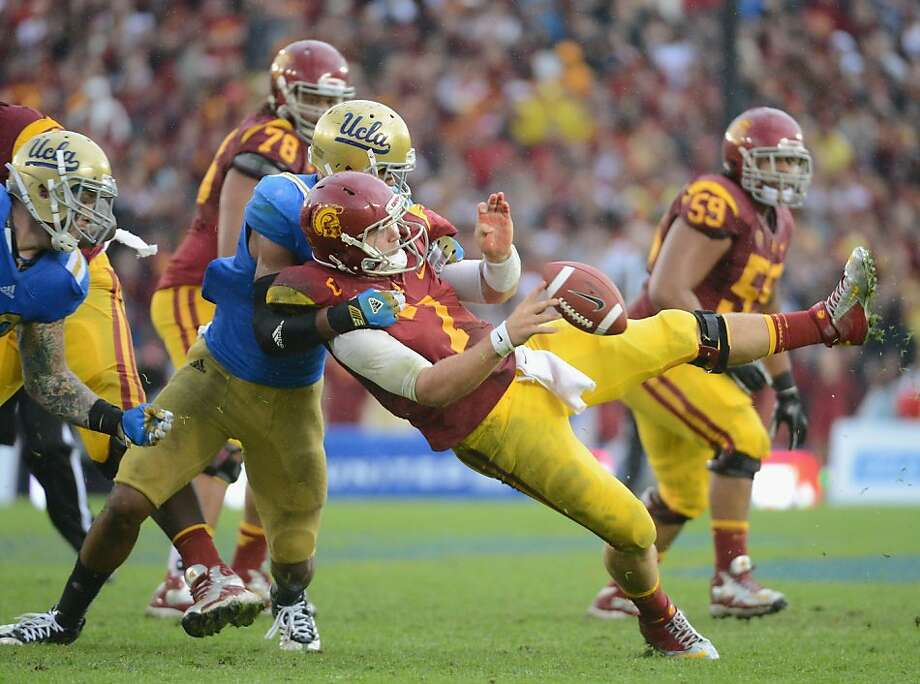 PASADENA, CA - NOVEMBER 17:  Matt Barkley #7 of the USC Trojans is hit by Anthony Barr #11 of the UCLA Bruins as he throws during the third quarter at Rose Bowl on November 17, 2012 in Pasadena, California.  (Photo by Harry How/Getty Images) Photo: Harry How, Getty Images