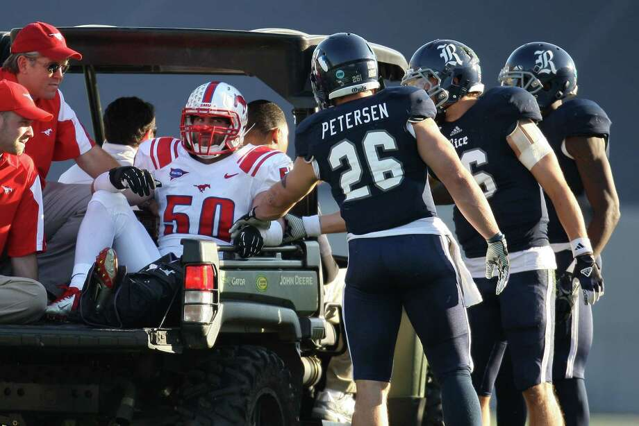 Rice's Turner Petersen (26) and teammates console SMU's Cameron Rogers as he is carted off the field after an injury during the first half of a Conference USA college football game, Saturday, November 17, 2012 at Rice Stadium in Houston, TX. Photo: Eric Christian Smith, For The Chronicle