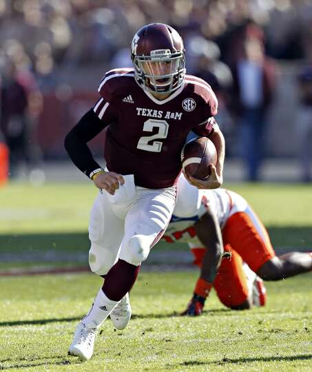 Johnny Manziel #2 of the Texas A&M Aggies looks for room to run against the Sam Houston State Bearka