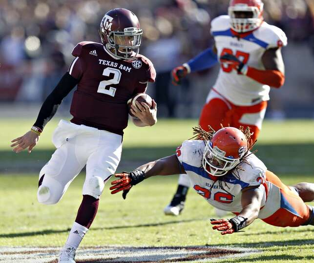 Johnny Manziel #2 of the Texas A&M Aggies avoids a tackle by Darius Taylor #36 of the Sam Houston St