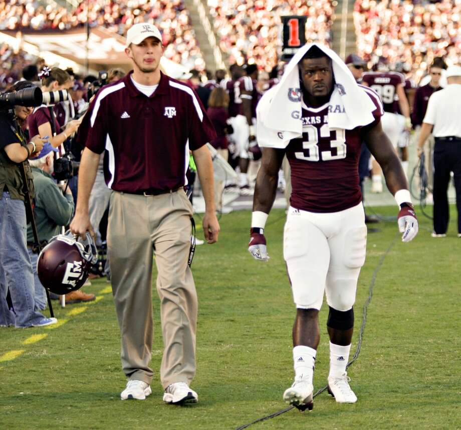 Christine Michael #33 of the Texas A&M Aggies is lead off the field after being ejected for striking a player after the play against the Sam Houston State Bearkats at Kyle Field on November 17, 2012 in College Station, Texas.  (Bob Levey / Getty Images)