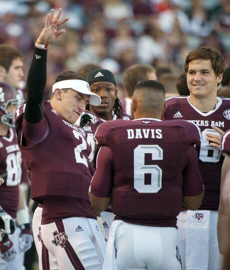 Texas A&M's Johnny Manziel, left, reacts on the bench after leaving the game during the third quarte