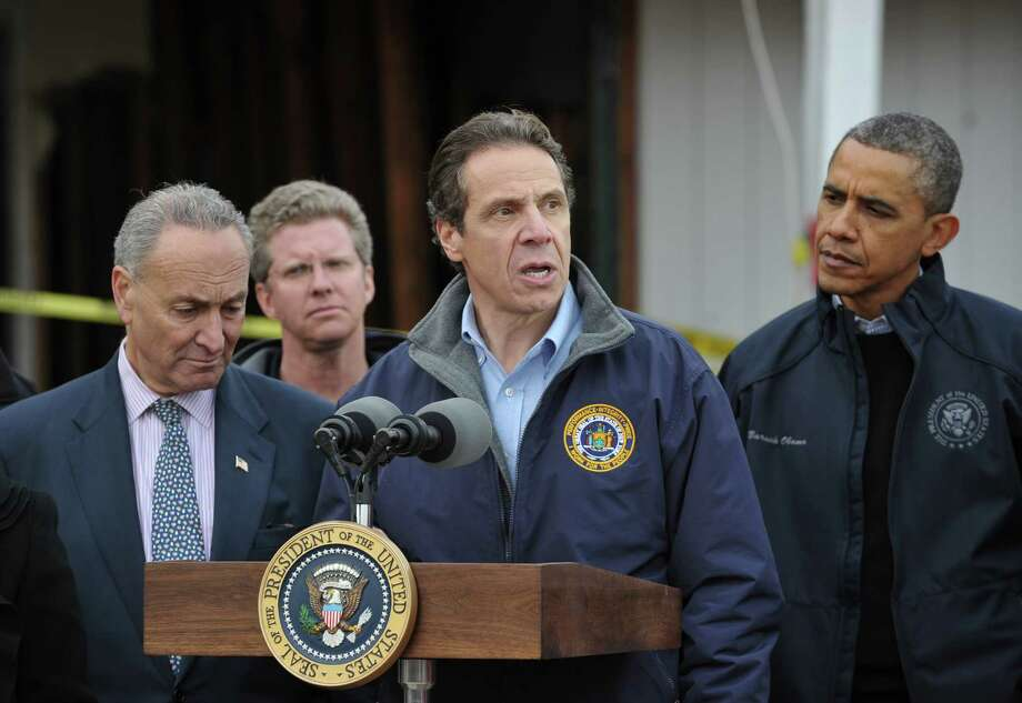 New York Governor Andrew Cuomo speaks following a visit to Cedar Grove Ave with US President Barack Obama to survey damage from Hurricane Sandy on Staten Island in New York City on November 15, 2012. From left are: Senator Chuck Schumer, D-NY, Housing and Urban Development Secretary Shaun Donovan, and Obama. AFP PHOTO/Mandel NGANMANDEL NGAN/AFP/Getty Images Photo: MANDEL NGAN