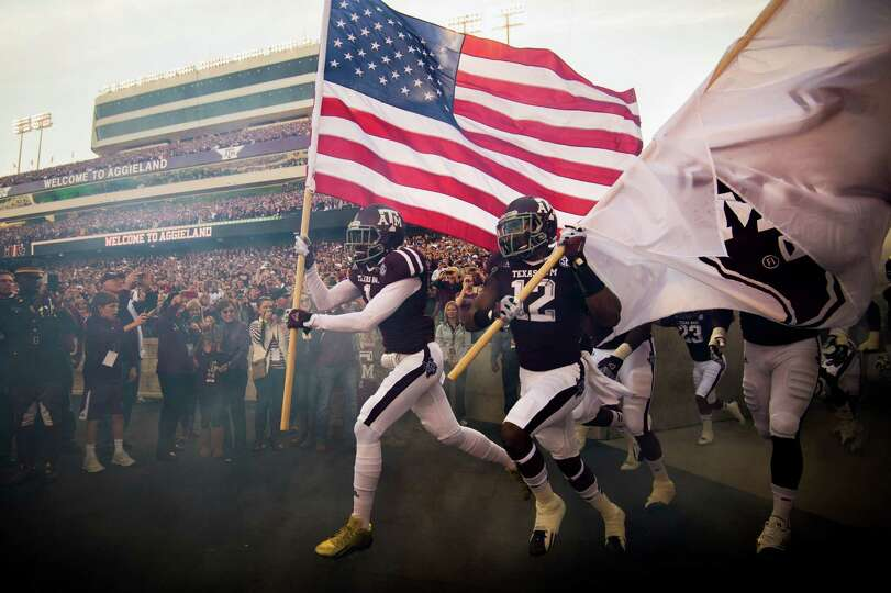 Texas A&M defensive back De'Vante Harris (1) catties the Stars and Stripes onto the field before fac