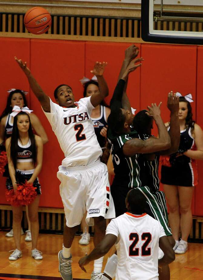 UTSA's Hyjii Thomas, left, jumps for a loose ball against South Carolina Upstate's defense during second half action at UTSA's Convocation Center on Saturday, Nov. 17, 2012. UTSA won 67-59. MICHAEL MILLER / FOR THE EXPRESS-NEWS Photo: Michael Miller, Express-News / © San Antonio Express-News