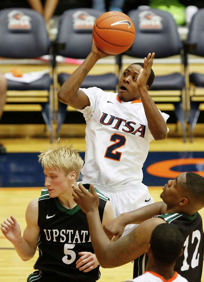 UTSA's Hyjii Thomas, center, gets a shot off over South Carolina Upstate's Ty Greene, left, and Ricardo Glenn during second half action at UTSA's Convocation Center on Saturday, Nov. 17, 2012. UTSA won 67-59. MICHAEL MILLER / FOR THE EXPRESS-NEWS Photo: Michael Miller, Express-News / © San Antonio Express-News