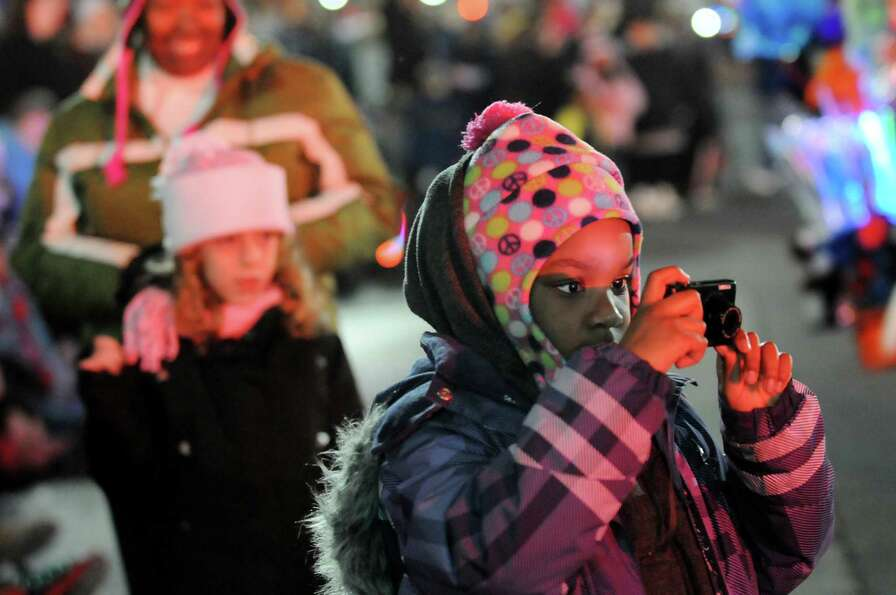 Kemahni Billups, 7, of Schenectady, right, takes pictures of the annual Gazette Holiday Parade on Sa