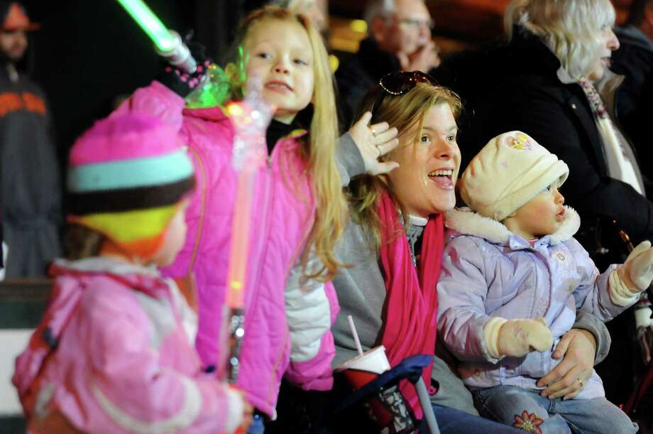Holly Carota of Schenectady, second from right, waves to participants in the annual Gazette Holiday Parade on Saturday, Nov. 17, 2012, in Schenectady, N.Y. Joining her are her children, from left, Gabriella, 4, Sydney, 7, and Emily, 1. (Cindy Schultz / Times Union) Photo: Cindy Schultz / 00019795A