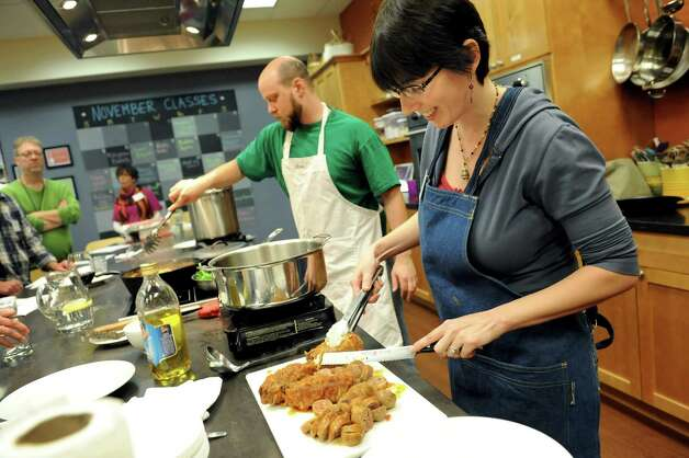 Cooking enthusiast Randy Kramer of Albany, right, slices hot and sweet Italian sausage as her husband, Mike Pierce, assists as Kramer creates her recipe for braciole al ragu over spinach and linguine during a cook-off on Saturday, Nov. 17, 2012, at Different Drummer's Kitchen in Guilderland, N.Y. Five finalists competed to have their dishes on the menu of Bellini's restaurant. (Cindy Schultz / Times Union) Photo: Cindy Schultz / 00020169A