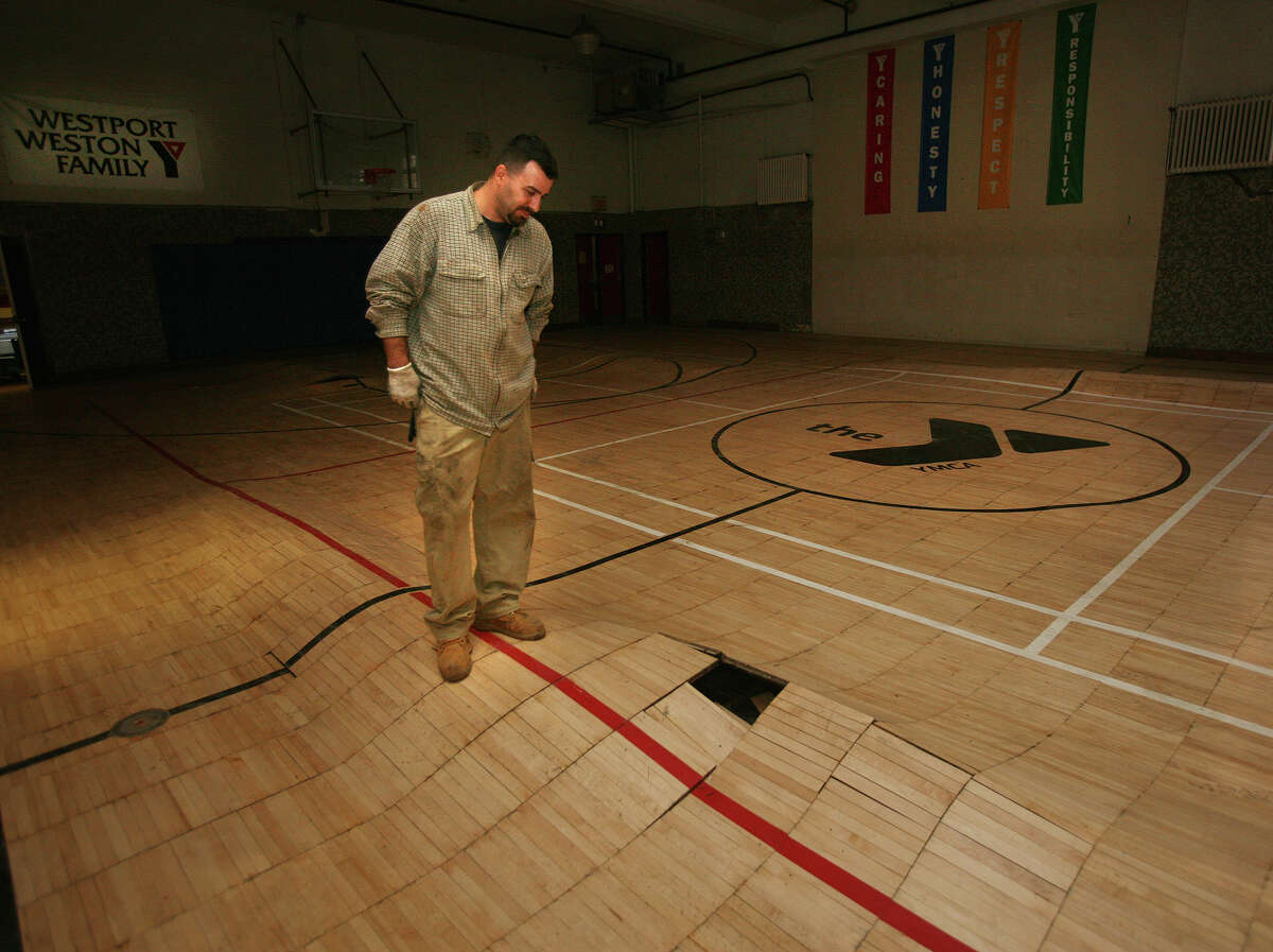 Craig Pietrowicz, an employee of Northeast Generator in Bridgeport, looks at the gym floor destroyed by flooding from Hurricane Sandy in the Westport Weston Family Y in downtown Westport on Wednesday, November 14, 2012.