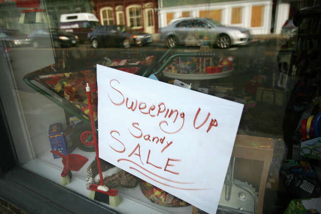 A Hurricane Sandy sale sign on the window of The Age of Reason store on the Post Road in downtown Westport on Thursday, November 15, 2012. Photo: Brian A. Pounds / Connecticut Post