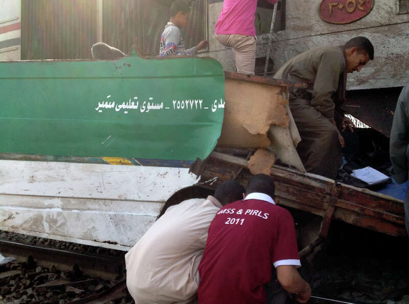 Egyptians inspect the wreckage after a speeding train crashed into a bus carrying children to their