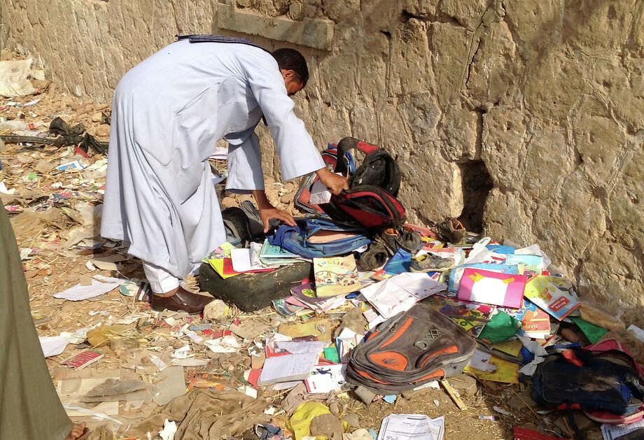 An Egyptian looks through books and school bags that were strewn along the tracks at the scene where a speeding train crashed into a bus carrying children to their kindergarten, killing at least 47, officials said, near Assiut  in southern Egypt, Saturday, Nov. 17, 2012. The bus was carrying more than 50 children between 4 and 6 years old when it was hit by a train near al-Mandara village in Manfaloot district in the province of Assiut, a security official said, adding that it appears that the railroad crossing was not closed as the train sped toward it. (AP Photo/Mamdouh Thabet) Photo: Mamdouh Thabet