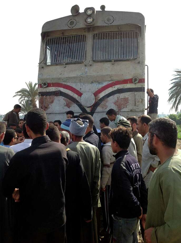Egyptians gather at the scene of a train crash that killed at least 47 people, most of them children near Assiut  in southern Egypt, Saturday, Nov. 17, 2012. The bus was carrying more than 50 children between 4 and 6 years old when it was hit near al-Mandara village in Manfaloot district in the province of Assiut, a security official said, adding that it appears that the railroad crossing was not closed as the train sped toward it. (AP Photo/Mamdouh Thabet) Photo: Mamdouh Thabet