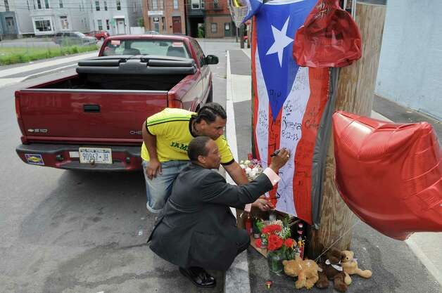 Rick Clark, left, helps Gregory Payne sign a flag at a street memorial for Luis Rivera, who was shot and killed by police in August 2011 at Grove Place in Schenectady, NY.   (Philip Kamrass / Times Union archive) Photo: Philip Kamrass / 00014274A