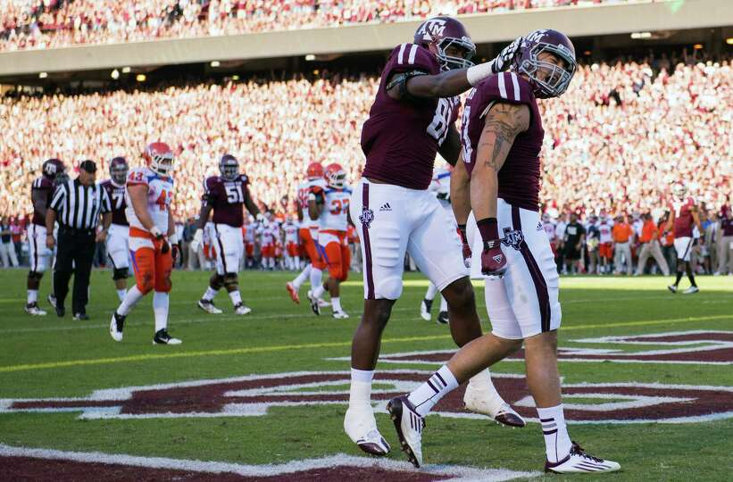 Texas A&M wide receiver Mike Evans (13) celebrates with tight end Nehemiah Hicks (81) after catching