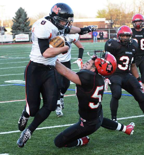 Glens Falls' linebacker #57 Lee Girard looses his helmet as he takes down Marlboro High's Austin Bec