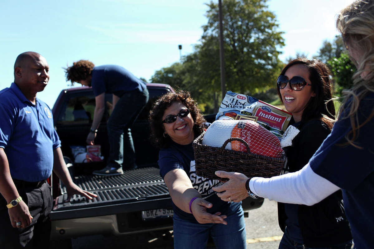 Employees of Security Service Federal Credit Union including Suzanne Stahl, from center, Audrey Perales and Jennifer Winslow accept donations of turkey baskets from the Prince Hall Freemasons, San Antonio Lodge 1, including Burrell Parmen, left, for the San Antonio Food Bank on Saturday, Nov. 17, 2012. Also helping unload, in truck, is Stahl's son, Cameron Stahl, 18.