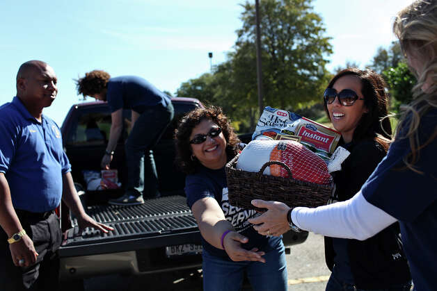 Employees of Security Service Federal Credit Union including Suzanne Stahl, from center, Audrey Perales and Jennifer Winslow accept donations of turkey baskets from the Prince Hall Freemasons, San Antonio Lodge 1, including Burrell Parmen, left, for the San Antonio Food Bank on Saturday, Nov. 17, 2012. Also helping unload, in truck, is Stahl's son, Cameron Stahl, 18. Photo: Lisa Krantz, San Antonio Express-News / © 2012 San Antonio Express-News
