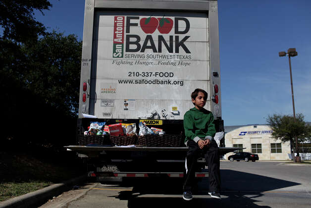 Mikee Dobratz, 10, the son of Security Service Federal Credit Union employee Elizabeth Dobratz, sits with food baskets donated by the Prince Hall Freemasons, San Antonio Lodge 1, as he volunteers with Credit Union employees to accept donations of turkeys, other food and cash for the San Antonio Food Bank on Saturday, Nov. 17, 2012. Photo: Lisa Krantz, San Antonio Express-News / © 2012 San Antonio Express-News