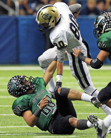 Panther receiver Alonso Roscoe rolls over Dragon defender Bryan Donnell as O'Connor plays Southwest in first round 5A playoff action at the Alamodome on November 17, 2012. Photo: Tom Reel, Express-News / ©2012 San Antono Express-News