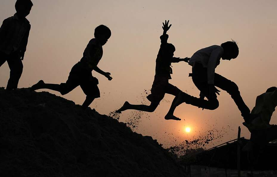 Indian children romp on the banks of the River Ganges in Allahabad.