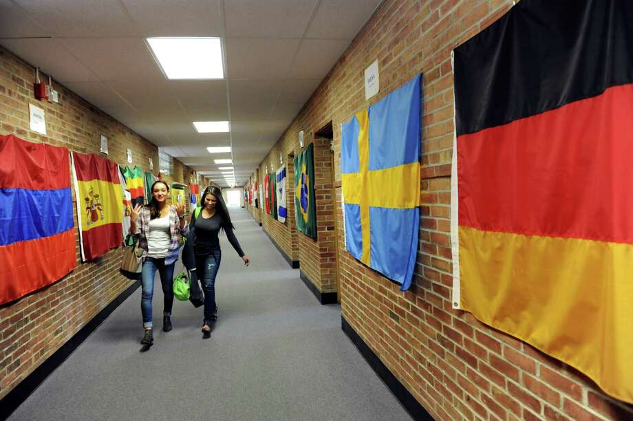 Exchange student Juliette Heyraud, 14, of France, left, talks with Rachel Bushm 14, of Newcomb as they walk through a hallway draped with flags from visiting students homelands on Tuesday, Sept. 11, 2012, at Newcomb Central School in Newcomb, N.Y. (Cindy Schultz / Times Union) Photo: Cindy Schultz / 00019204A