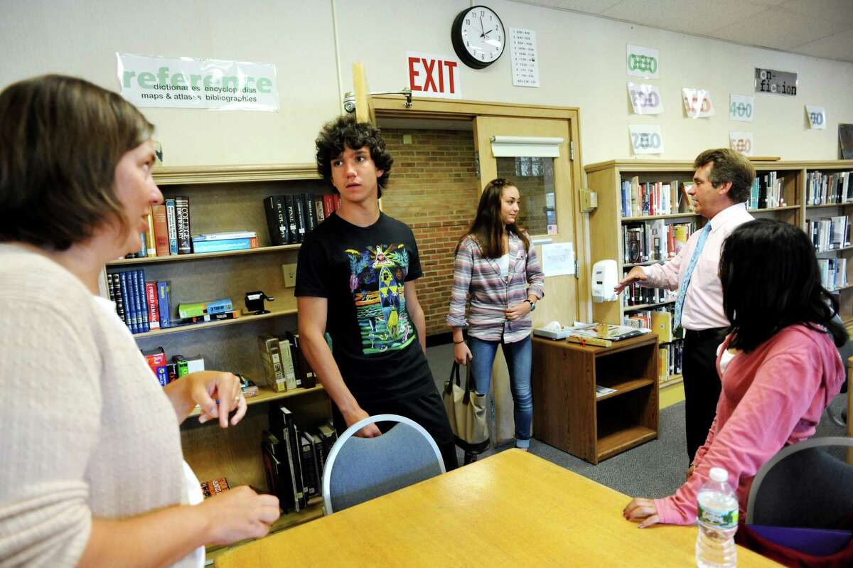 Librarian Autumn Goerner, left, talks with Federico Portera, 17, second from left, of Italy about study hall time on Tuesday, Sept. 11, 2012, at Newcomb Central School in Newcomb, N.Y. Joining them are Juliette Heyraud, 14, of France, center, math teacher Ed LaCourse and Gabriela Espana, 15. (Cindy Schultz / Times Union)