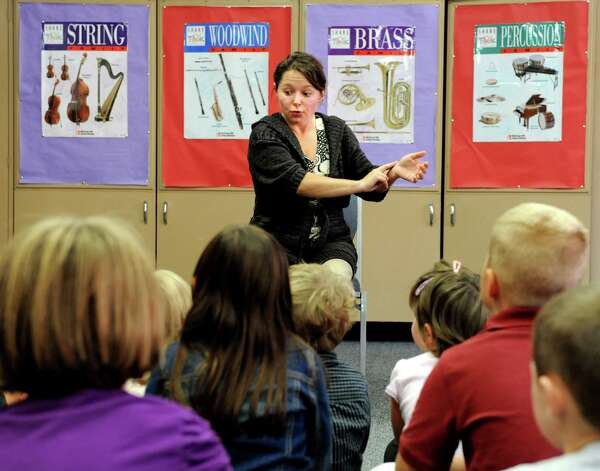 Music teacher Zhanna Pendell of Belarus, center, encourages young students to feel the pulse in their arms as a way to learn the beat of music on Tuesday, Sept. 11, 2012, at Newcomb Central School in Newcomb, N.Y. (Cindy Schultz / Times Union) Photo: Cindy  Schultz / 00019204A