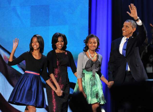 US President Barack Obama accompanied by daughter Malia, First Lady Michelle and daughter Sasha waves to supporters as he arrives on stage on election night November 6, 2012 in Chicago, Illinois. President Barack Obama swept to re-election Tuesday, forging history again by transcending a slow economic recovery and the high unemployment which haunted his first term to beat Republican Mitt Romney. AFP PHOTO/Jewel SamadJEWEL SAMAD/AFP/Getty Images Photo: JEWEL SAMAD, AFP/Getty Images / AFP