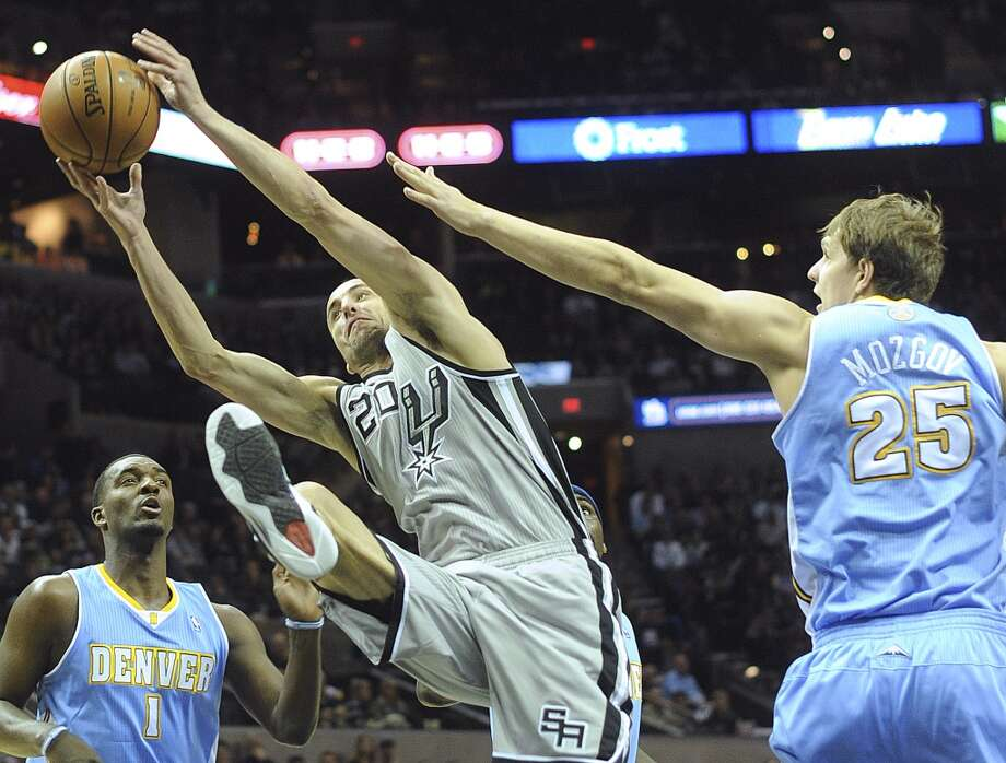Manu Ginobili (20) of the San Antonio Spurs drives to the basket as Timofey Mozgov (25) of the Denver Nuggets fouls him during firstl-half NBA action in the Alamodome on Nov. 17, 2012. (Billy Calzada / San Antonio Express-News)