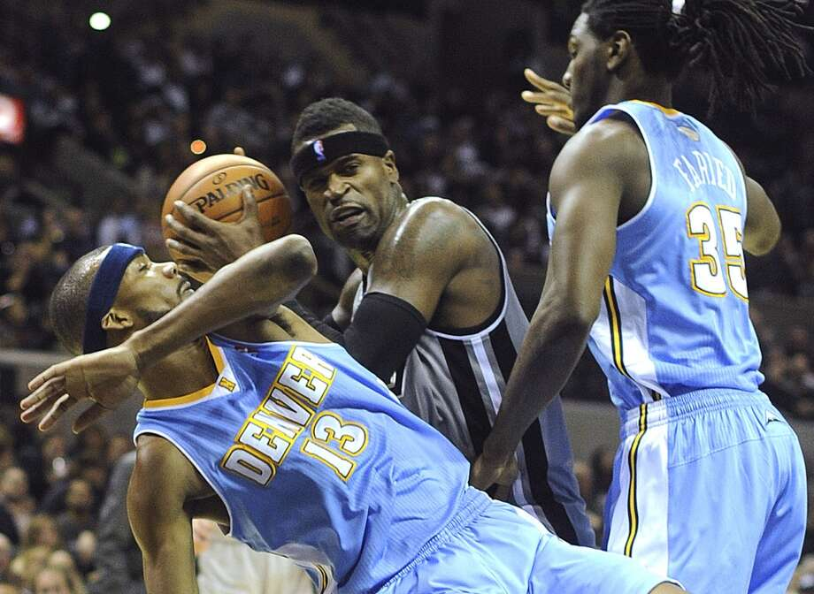 Stephen Jackson of the San Antonio Spurs looks to shoot as Corey Brewer (13) and Kenneth Faried (35) of the Denver Nuggets defend during NBA action in the Alamodome on Nov. 17, 2012. (Billy Calzada / San Antonio Express-News)