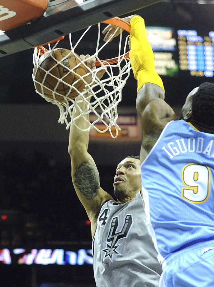 Danny Green of the San Antonio Spurs dunks as Andre Iguodala of the Denver Nuggets defends during first-quarter NBA action in the Alamodome on Nov. 17, 2012. (Billy Calzada / San Antonio Express-News)