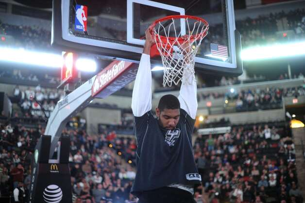 Tim Duncan of the San Antonio Spurs hangs from the rim before team introductions in preparation for the team's game against the Denver Nuggets in the Alamodome on Saturday, Nov. 17, 2012. (Billy Calzada / San Antonio Express-News)