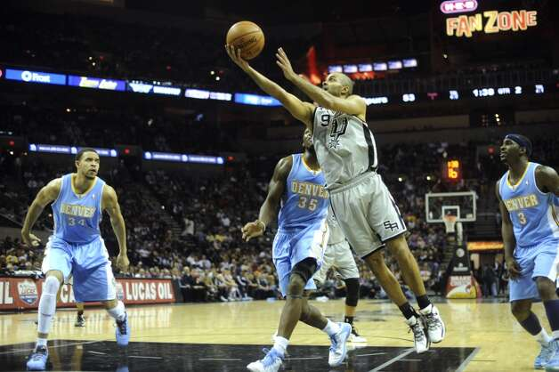 Tony Parker of the San Antonio Spurs drives and shoots as JaVale McGee (34) Kenneth Faried (35) and Ty Lawson (3) of the Denver Nuggets defend during NBA action in the Alamodome on Nov. 17, 2012. (Billy Calzada / San Antonio Express-News)