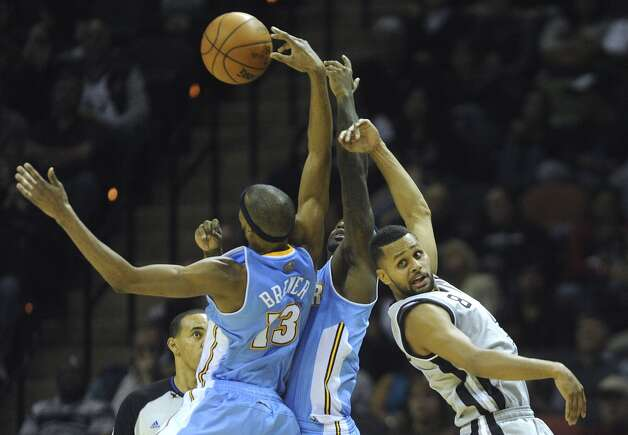 San Antonio Spurs guard Patty Mills, right, battles Corey Brewer (13) and Ty Lawson of the Denver Nuggets for the ball during NBA action in the Alamodome on Saturday, Nov. 17, 2012. (Billy Calzada / San Antonio Express-News)