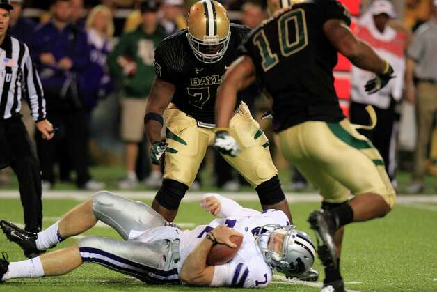 Kansas State quarterback Collin Klein (7) lays on the turf after he was sacked by Baylor defensive end Chris McAllister, not shown, with Nick Johnson (76) and Gary Mason Jr. (10) looking on during the third quarter of an NCAA college football game, Saturday, Nov. 17, 2012, in Waco Texas. (AP Photo/LM Otero) Photo: LM Otero, Associated Press / AP