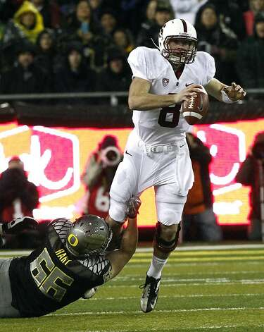Stanford quarterback Kevin Hogan, right, is tackled by Oregon defender Taylor Hart during the first half of  an NCAA college football game in Eugene, Ore., Saturday, Nov. 17, 2012.(AP Photo/Don Ryan) Photo: Don Ryan, Associated Press