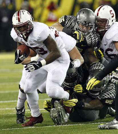 Stanford running back Stepfan Taylor, left, breaks away from Oregon defenders during the first half of their NCAA college football game in Eugene, Ore., Saturday, Nov. 17, 2012. (AP Photo/Don Ryan) Photo: Don Ryan, Associated Press