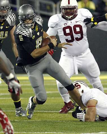 Oregon quarterback Marcus Mariota, left, is grabbed by the foot by Stanford defender Shayne Skov during the first half of their NCAA college football game in Eugene, Ore., Saturday, Nov. 17, 2012.(AP Photo/Don Ryan) Photo: Don Ryan, Associated Press