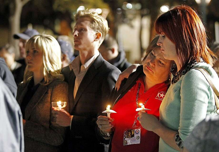 People gather in Centennial Plaza in Midland, Texas on Saturday, Nov. 17, 2012 for a candlelight vigil held in honor of four veterans who were killed when a freight train hit a parade float Thursday. (AP Photo/Midland Reporter-Telegram, James Durbin) Photo: James Durbin, Associated Press