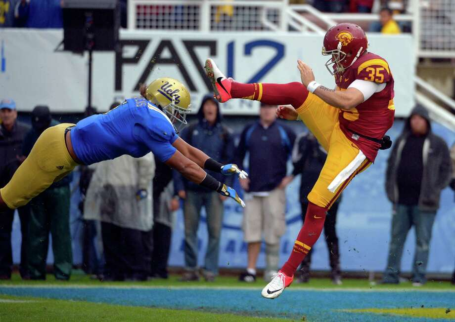 UCLA linebacker Eric Kendricks, left, blocks a punt by Southern California's Kris Albarado during the second half of their NCAA college football game, Saturday, Nov. 17, 2012, in Pasadena, Calif. UCLA won 38-28. (AP Photo/Mark J. Terrill) Photo: Mark J. Terrill, STF / AP
