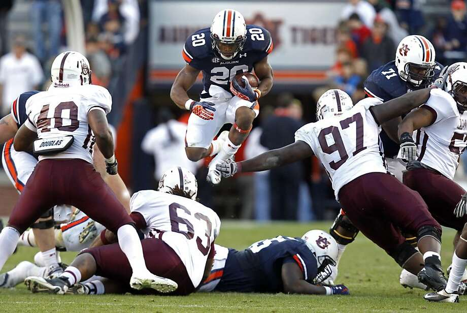 Auburn running back Corey Grant (20) jumps over the pile for extra yardage during the second half of an NCAA college football game against ALabama A&M on Saturday, Nov. 17, 2012 in Auburn, Ala. Auburn defeated Alabama A&M 51-7. (AP Photo/Butch Dill) Photo: Butch Dill, Associated Press