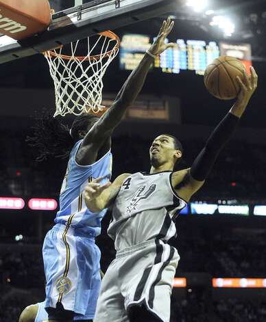 Danny Green of the Spurs, right, shoots as Kenneth Faried of the Denver Nuggets attempts to block his shot in the Alamodome on Nov. 17, 2012. (Billy Calzada / San Antonio Express-News)