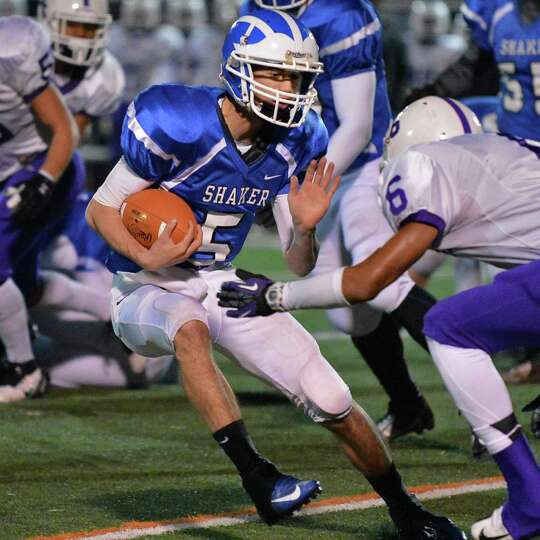 Shaker quarterback #5 Chris Landers runs into a tough  New Rochelle defense during the Class AA stat