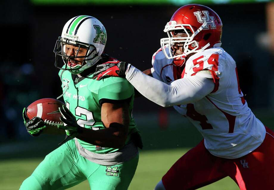 Marshall's Essray Taliaferro is stopped by Houston defender Everett Daniels during an NCAA college football game on Saturday, Nov. 17, 2012, at Joan C. Edwards Stadium in Huntington, W.Va. Marshall won 44-41. (AP Photo/The Herald-Dispatch, Mark Webb) Photo: Mark Webb, Associated Press / Herald Dispatch