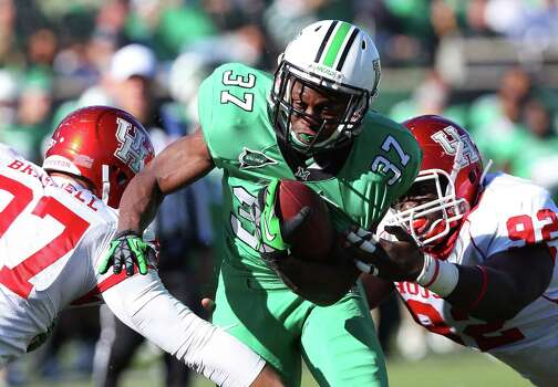 Marshall running back Kevin Grooms (37) rushes against Houston defenders Eric Braswell (97) and Joey Mbu (92) during an NCAA college football game on Saturday, Nov. 17, 2012, at Joan C. Edwards Stadium in Huntington, W.Va. Marshall won 44-41. (AP Photo/The Herald-Dispatch, Mark Webb) Photo: Mark Webb, Associated Press / Herald Dispatch