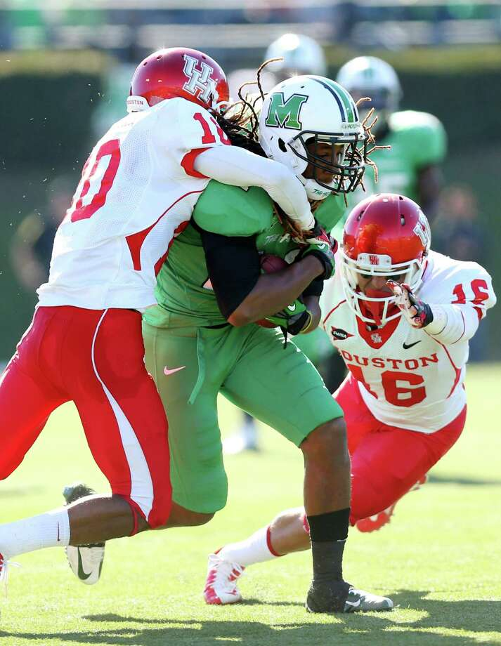 Marshall receiver Isaiah King (24) is stopped by Houston defenders Zach McMillian (10) and Adrian McDonald (16) during an NCAA college football game on Saturday, Nov. 17, 2012, at Joan C. Edwards Stadium in Huntington, W.Va. Marshall won 44-41. (AP Photo/The Herald-Dispatch, Mark Webb) Photo: Mark Webb, Associated Press / Herald Dispatch