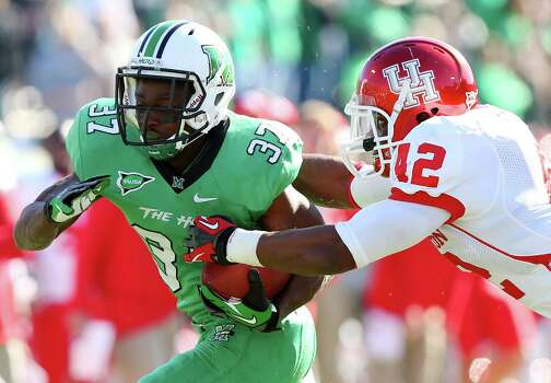 Marshall running back Kevin Grooms is stopped by Houston defender Phillip Steward during an NCAA college football game on Saturday, Nov. 17, 2012, at Joan C. Edwards Stadium in Huntington, W.Va. Marshall won 44-41. (AP Photo/The Herald-Dispatch, Mark Webb) Photo: Mark Webb, Associated Press / Herald Dispatch