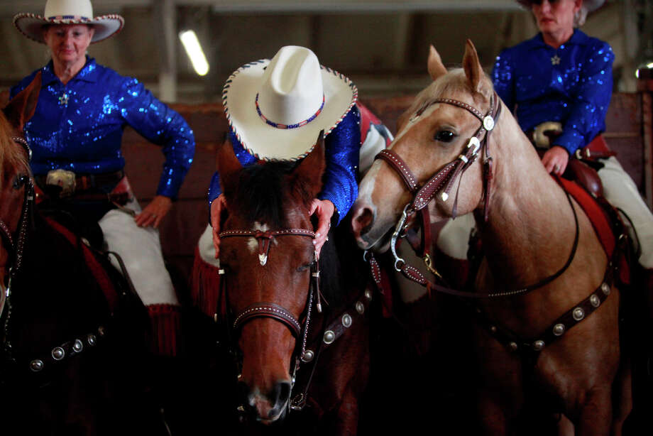 Cathy Fairbanks (ctr) with the California Cowgirls adjust the bridal on her horse at The Grand National Drill Team Jackpot held at the Cow Palace. Photo: Mike Kepka, The Chronicle / ONLINE_YES